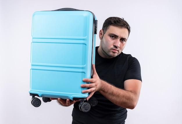 Jonge reiziger man in zwarte t-shirt bedrijf koffer verbaasd staande over witte muur