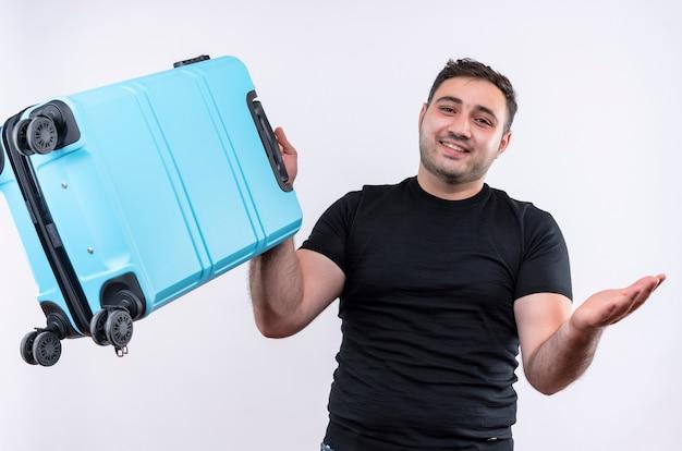 Jonge reiziger man in zwarte t-shirt met koffer glimlachend vrolijk spreidend met arm naar de zijkant staande over witte muur