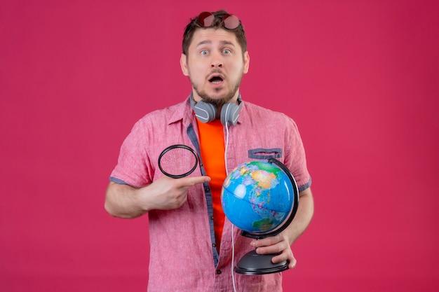 Jonge reiziger man met koptelefoon bedrijf globe en vergrootglas kijken camera verrast en verbaasd staande over roze achtergrond