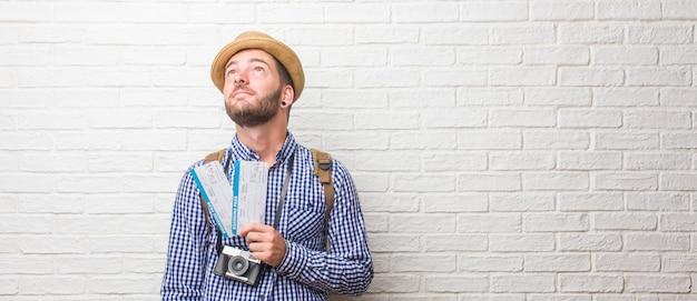 Jonge reiziger man met rugzak en een vintage camera opzoeken, denken aan iets leuks en het hebben van een idee, concept van verbeelding, blij en opgewonden. een instapkaart houden.