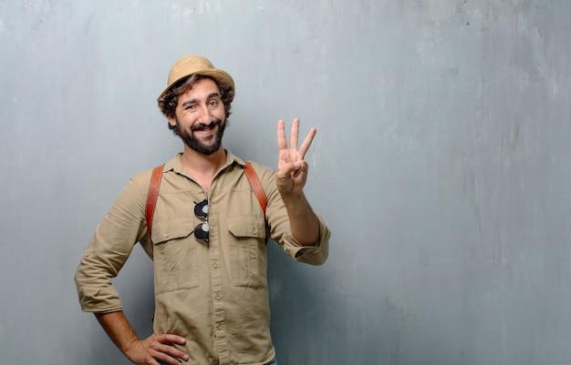 Jonge reiziger man of toerist glimlachen, tellen nummer drie met vingers.