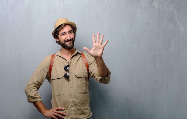 Jonge reiziger man of toerist glimlachen, tellen nummer vijf met vingers, met een open palm