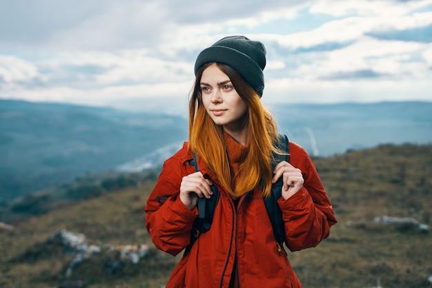 Jonge reiziger met rugzak en bergen in de wolken van de achtergrondlandschapshemel