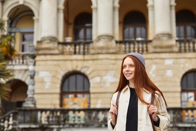 Jonge reiziger met rugzak op haar schouder die architecturale monumentenplaats verkent tijdens langverwachte...