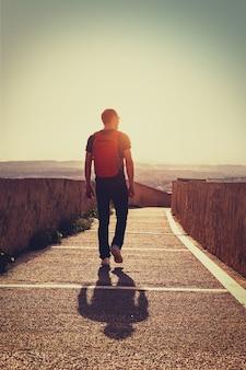 Jonge reiziger met rugzak wandelen langs de weg bij zonsondergang