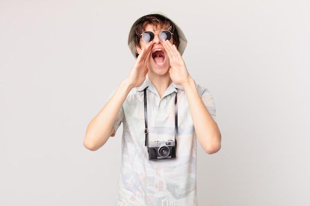 Jonge reiziger of toerist die zich gelukkig voelt, een grote schreeuw geeft met de handen naast de mond