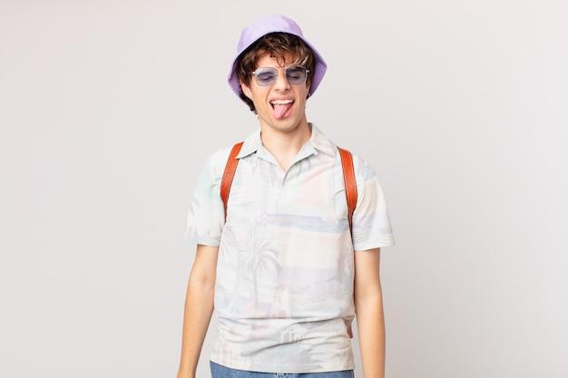 Jonge reiziger of toerist met vrolijke en rebelse houding, grappen maken en tong uitsteken