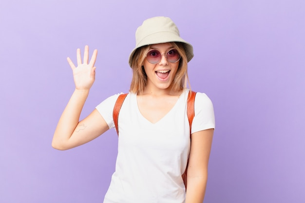 Jonge reiziger toeristische vrouw glimlachend gelukkig zwaaiende hand welkom heten en begroeten