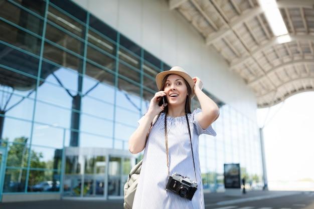 Jonge reiziger toeristische vrouw met retro vintage fotocamera klampt zich vast aan het hoofd praten op mobiel telefoongesprek vriend