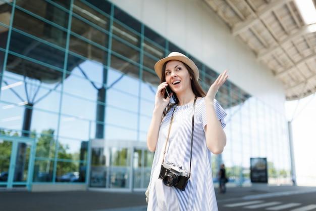 Jonge reiziger toeristische vrouw met retro vintage fotocamera spreidende handen praten op mobiel telefoontje vriend