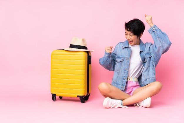 Jonge reiziger vietnamese vrouw met koffer zittend op de vloer over geïsoleerde roze muur viert een overwinning