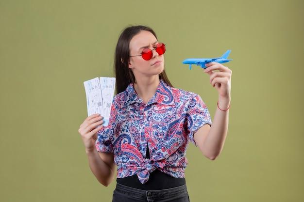 Jonge reiziger vrouw draagt ?? rode zonnebril met kaartjes en speelgoed vliegtuig te kijken met peinzende uitdrukking met fronsend gezicht staande over groene achtergrond