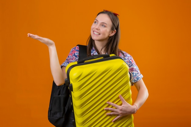 Jonge reiziger vrouw dragen rode zonnebril op hoofd staande met rugzak bedrijf koffer opzij kijken en presenteren met arm van de hand iets glimlachend met blij gezicht over oranje pagina