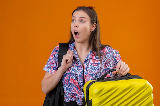 Jonge reiziger vrouw dragen rode zonnebril op hoofd staande met rugzak bedrijf koffer opzij kijken verrast en verbaasd met wijd open mond en ogen over oranje achtergrond