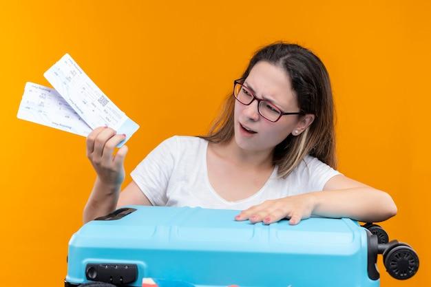 Jonge reiziger vrouw in wit t-shirt bedrijf koffer vol en vliegtickets kijken naar hen met sceptische uitdrukking staan