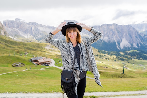 Jonge reiziger vrouw met hoed en rugzak genieten van geweldig uitzicht op de bergen