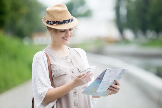 Jonge reiziger vrouw met kaart en telefoon tijdens het buitenland reis
