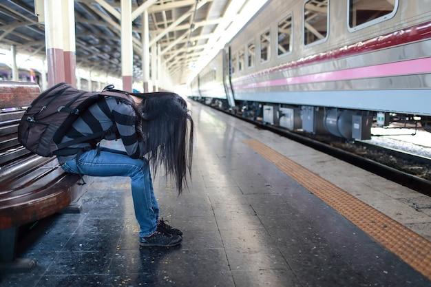 Jonge reiziger vrouw met rugzak depressief en benadrukt tijdens het wachten op de trein
