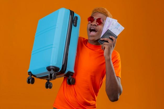 Jonge reizigersjongen die de oranje koffer van de t-shirtholding en vliegtuigkaartjes draagt die verbaasd en verbaasd over oranje muur staan kijken