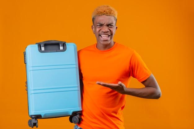 Jonge reizigersjongen die een oranje t-shirt draagt en een koffer vasthoudt die het presenteert met de arm van zijn hand, ontevreden gevoel geïrriteerd staande over oranje muur