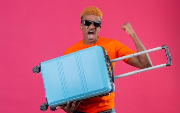 Jonge reizigersjongen die oranje de koffer draagt die van de t-shirtholding gebalde vuist houdt gek gelukkig geschreeuw die zich over roze muur bevindt
