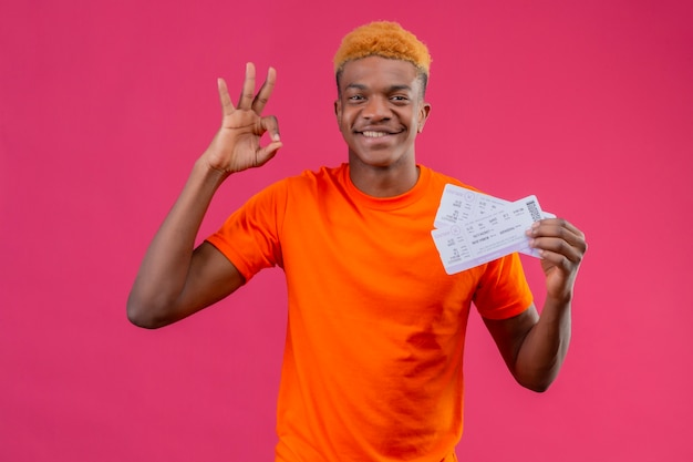 Jonge reizigersjongen die oranje de vliegtuigkaartjes van de t-shirtholding draagt die vrolijk glimlachen doet ok teken dat zich over roze muur bevindt
