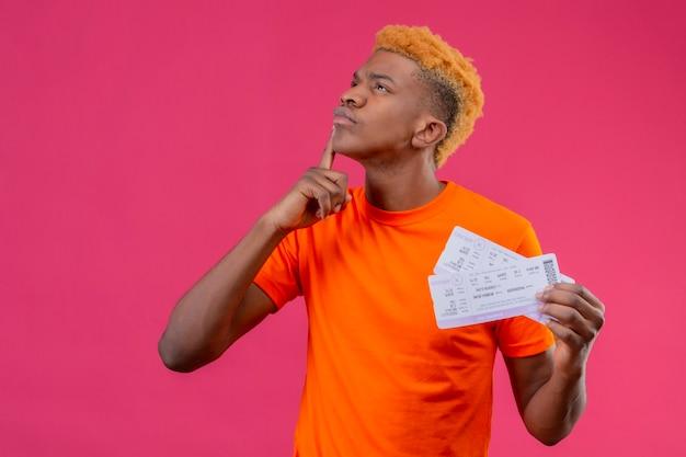 Jonge reizigersjongen die oranje t-shirt draagt die vliegtuigkaartjes houdt die met vinger op kin met peinzende uitdrukking op gezicht opkijken die zich over roze muur bevindt
