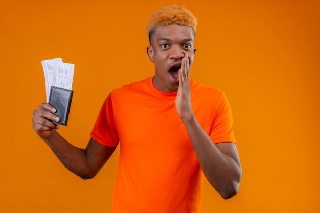 Jonge reizigersjongen die oranje t-shirt draagt die vliegtuigkaartjes houdt die verbaasd en verrast kijkt die mond behandelt met hand die zich over oranje muur bevindt