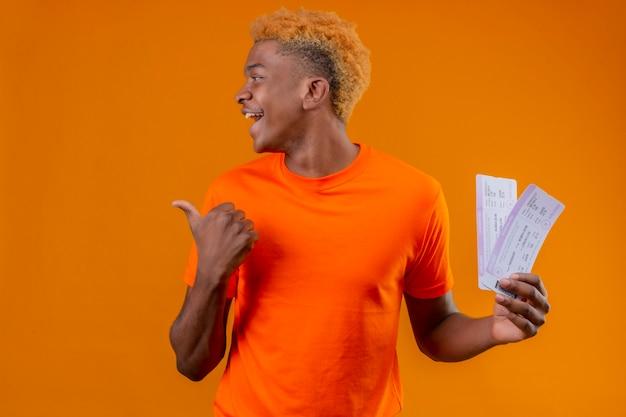 Jonge reizigersjongen die oranje t-shirt draagt die vliegtuigtickets houdt die opzij glimlachend vrolijk richtend met duim naar de kant over oranje muur kijkt