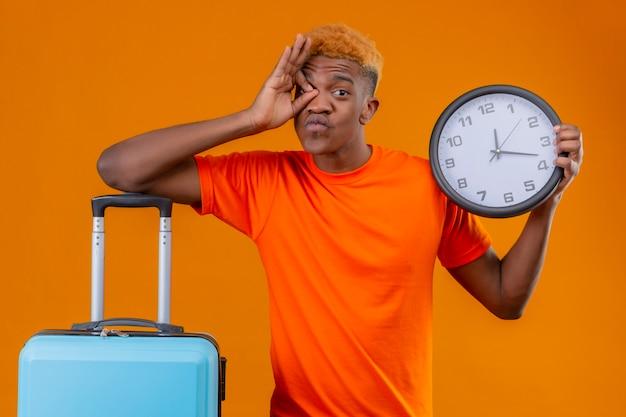Jonge reizigersjongen die oranje t-shirt draagt die zich met de klok optimistisch en vrolijk van de kofferholding bevindt die ok teken door dit teken over oranje muur doet