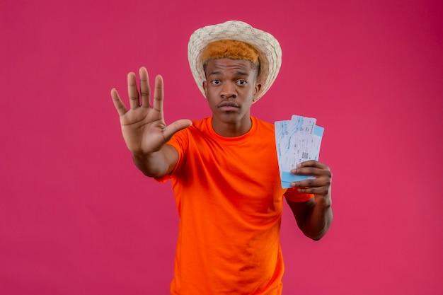 Jonge reizigersjongen die oranje t-shirt dragen die vliegtuigtickets houden die stopbord met hand maken die bezorgd over roze muur staan kijken