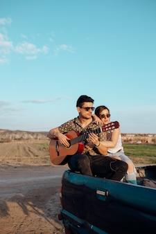 Jonge reizigersliefhebbers die pret hebben die de gitaar bovenop jeep 4x4 auto spelen. paar dat een reislustige vakantie maakt bij de zomer