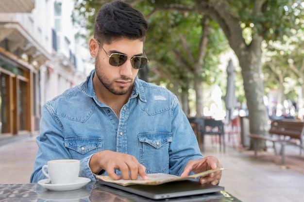 Jonge reizigersman zit op een caféterras en plant haar reis met kaart en laptop