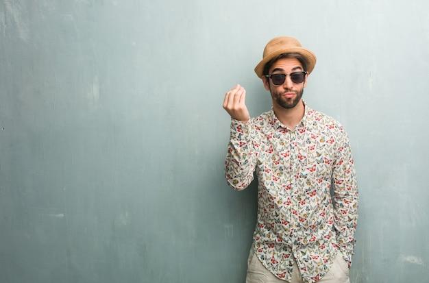 Jonge reizigersmens die een kleurrijk overhemd draagt dat een typisch italiaans gebaar, het glimlachen doet