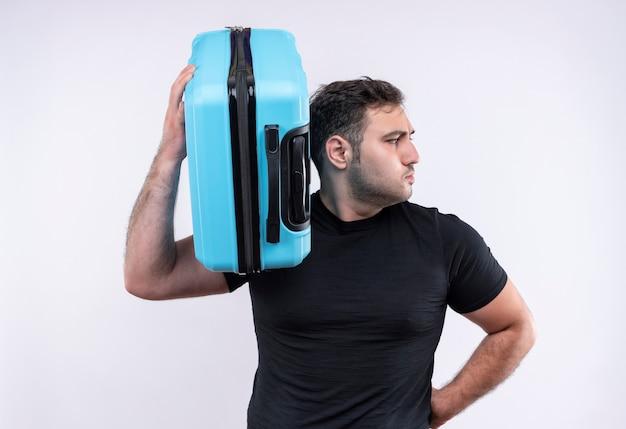 Jonge reizigersmens die in de zwarte koffer van de t-shirtholding opzij met ernstig gezicht kijken dat zich over witte muur bevindt