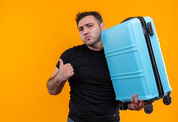 Jonge reizigersmens die in zwart de koffer van de t-shirtholding verward kijkt die met duim terug wijst die zich over oranje muur bevindt