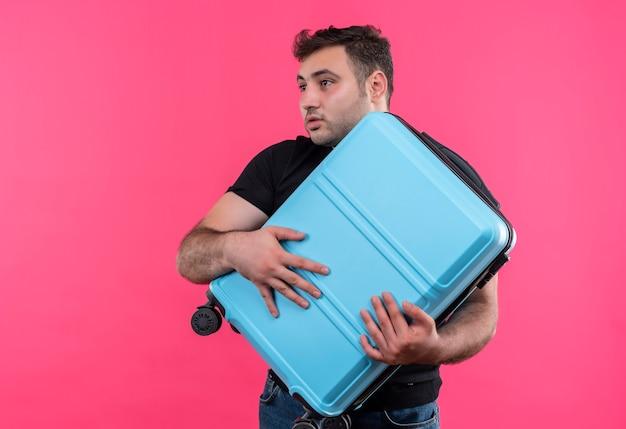 Jonge reizigersmens die in zwarte koffer van de t-shirtholding opzij kijkt verward met vreesuitdrukking die zich over roze muur bevindt