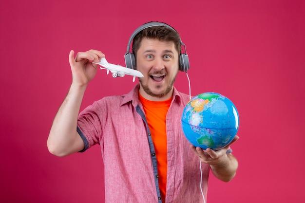 Jonge reizigersmens die met hoofdtelefoons bol en stuk speelgoed vliegtuig houden vreugdevol en gelukkig kijken camera die zich over roze achtergrond bevindt