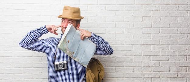 Jonge reizigersmens die rugzak en een uitstekende camera draagt die oren behandelen met handen, boos en vermoeid van het horen van wat geluid. een kaart vasthouden.