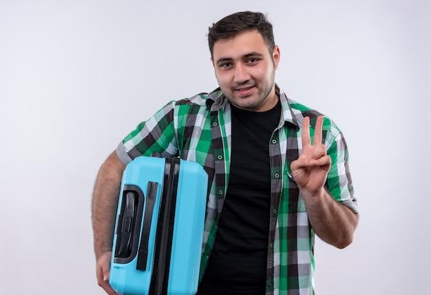 Jonge reizigersmens in de ingecheckte koffer die van de overhemdsholding en met vinger nummer twee omhoog wijst die zich over witte muur glimlachen