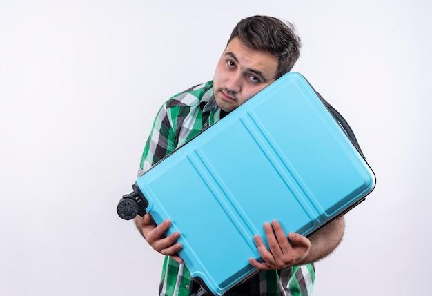 Jonge reizigersmens in de ingecheckte koffer van de overhemdsholding met droevige uitdrukking op gezicht dat zich over witte muur bevindt