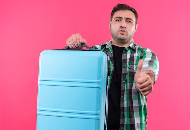 Jonge reizigersmens in de ingecheckte koffer van de overhemdsholding met ernstig gezicht die duimen tonen die zich over roze muur bevinden