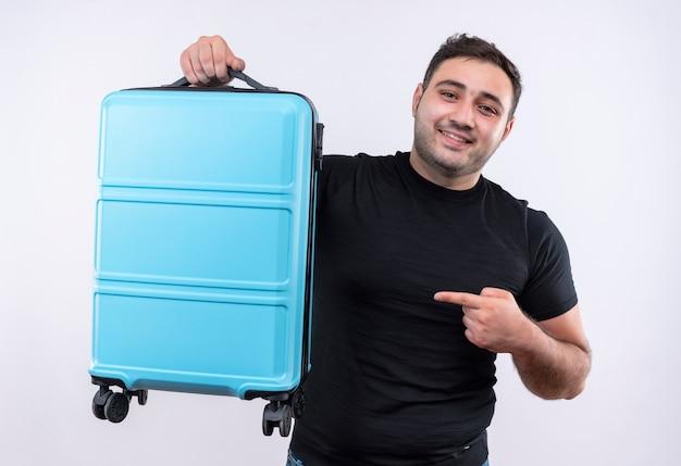 Jonge reizigersmens in de zwarte koffer die van de t-shirtholding met vinger ernaar richt glimlachend zelfverzekerd over witte muur