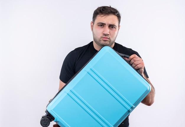 Jonge reizigersmens in de zwarte koffer van de t-shirtholding met ernstig fronsend gezicht dat zich over witte muur bevindt