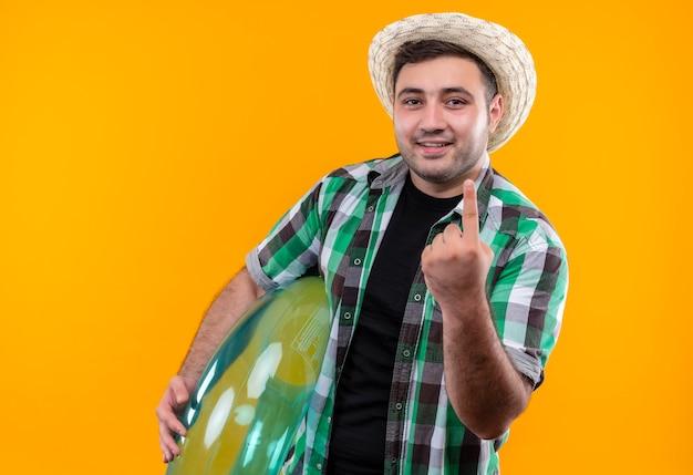 Jonge reizigersmens in gecontroleerd overhemd en de zomerhoed die opblaasbare ring houden die tonend wijsvinger glimlachen die zich over oranje muur bevindt