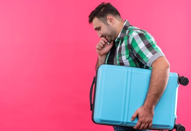 Jonge reizigersmens in geruit overhemd die koffer zijwaarts met peinzende uitdrukking op gezicht over roze muur houden
