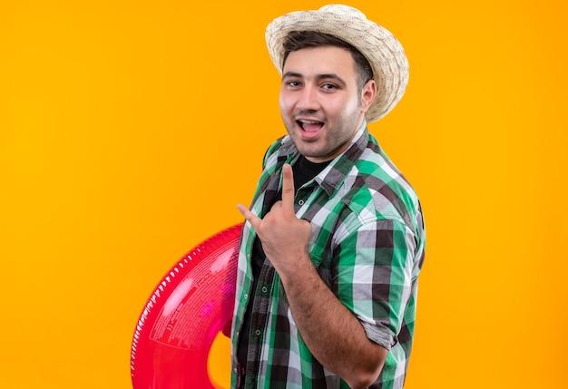 Jonge reizigersmens in geruit overhemd en zomerhoed die opblaasbare ring blij en verlaten houdt die rotssymbool met vingers toont die zich over oranje muur bevinden