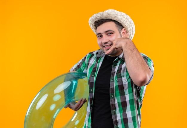 Jonge reizigersmens in geruit overhemd en zomerhoed die opblaasbare ring houden die vrolijk glimlachend bel me gebaar maakt die zich over oranje muur bevinden