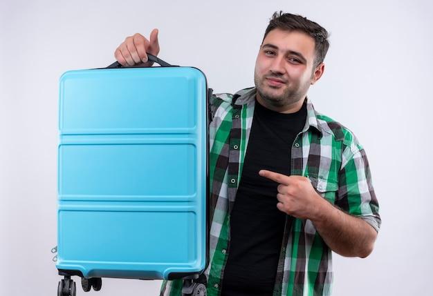 Jonge reizigersmens in ingecheckte overhemdsholding die koffer met wijsvinger ernaar richt met zelfverzekerde glimlach op gezicht dat zich over witte muur bevindt