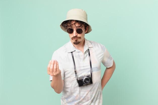 Jonge reizigerstoerist die een capice of geldgebaar maakt en zegt dat u moet betalen